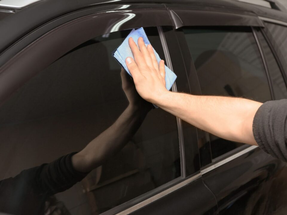 an auto detailer polishing a car with ceramic window tint