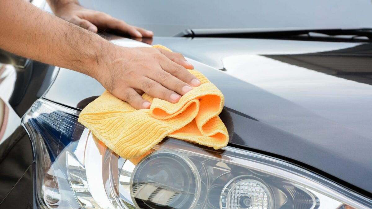 a man cleaning a car with a microfiber cloth during a full detail