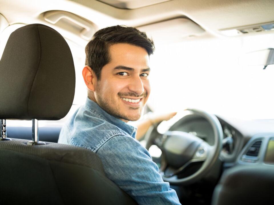 a smiling man driving away