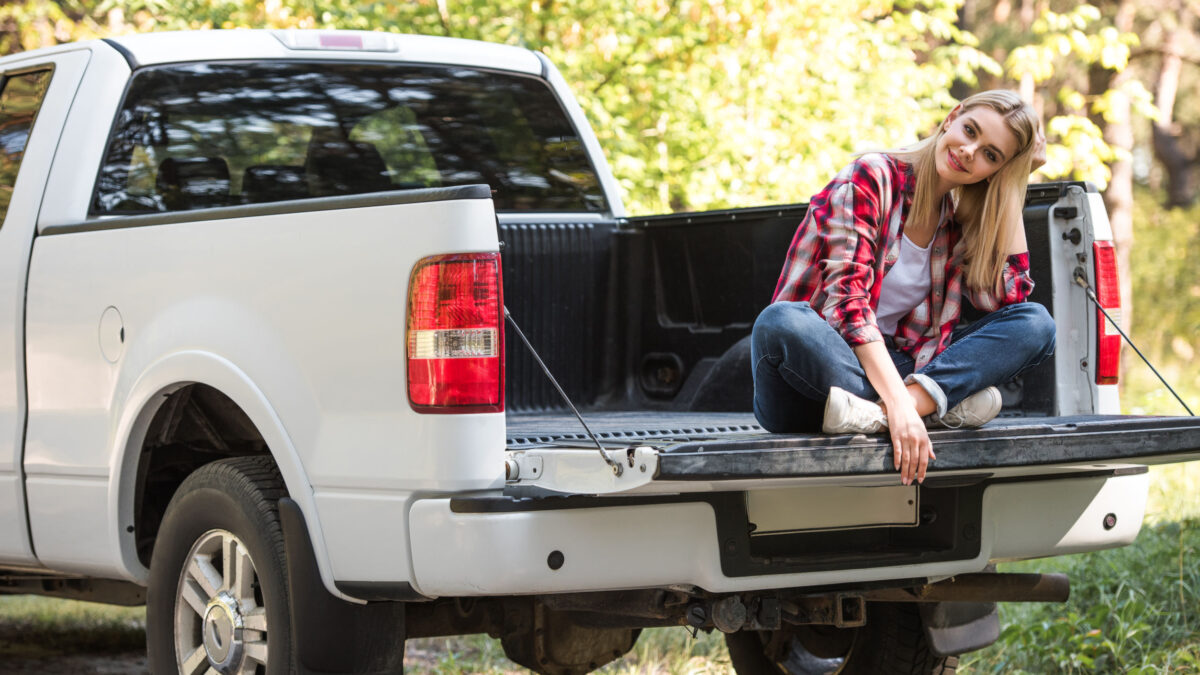 a young woman in plaid sitting on the tailgate of her truck