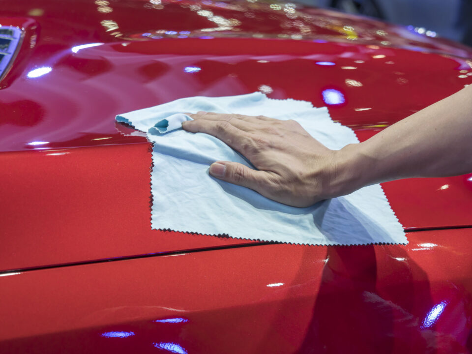 detailing a shiny red car and using a microfiber cloth