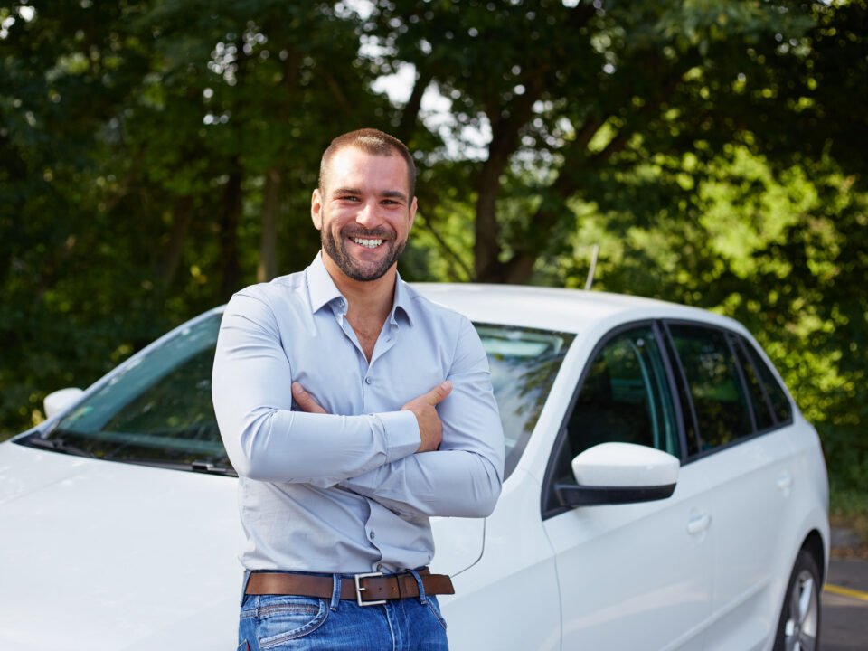 a smiling man standing in front of his car with tinted windows